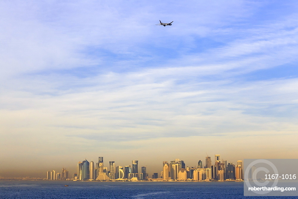 Jet airplane after take off from Hamad International Airport, seen above Doha city skyline from the sea, Qatar, Middle East