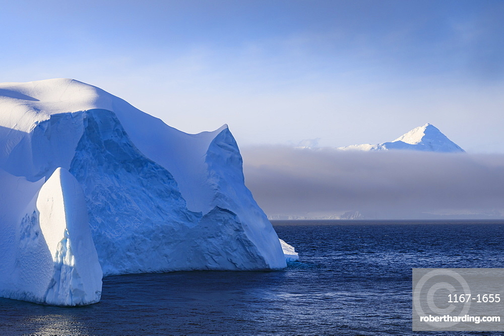 Huge iceberg, and mountain, clearing mist, Bransfield Strait, near South Shetland Islands and Antarctic Peninsula, Antarctica, Polar Regions