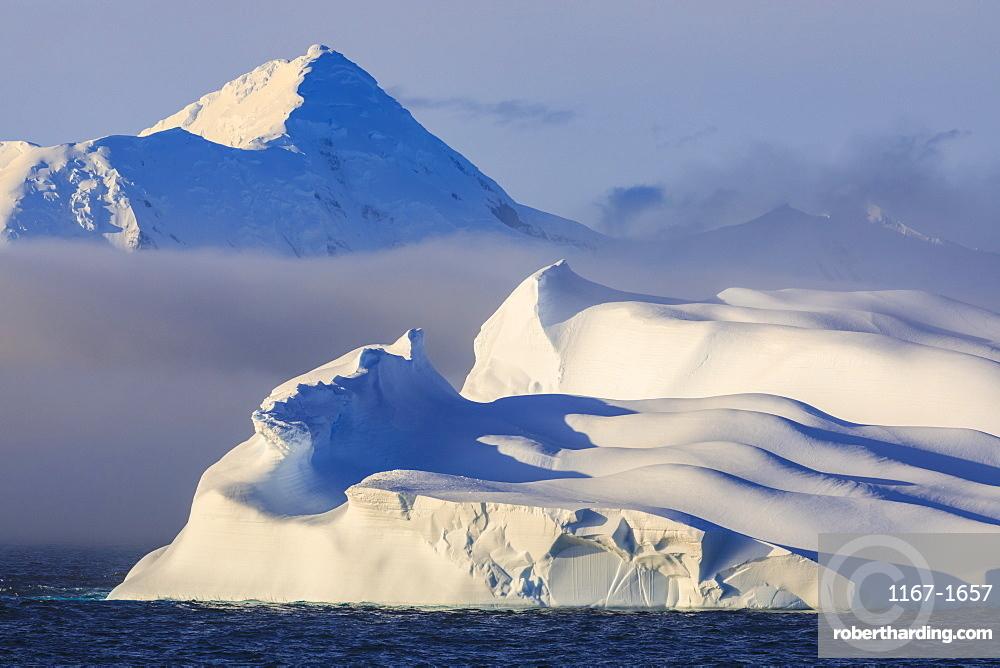 Huge non-tabular iceberg, mountains, evening light and mist, Bransfield Strait, South Shetland Islands, Antarctica, Polar Regions