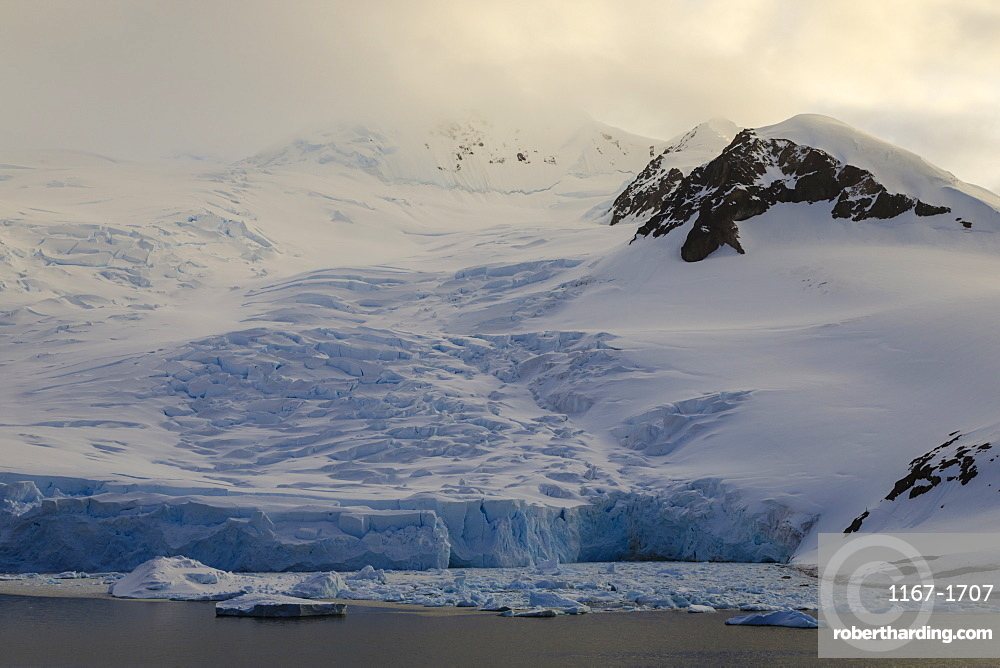Glacier at sunrise, with atmospheric cloud and mist, Neko Harbour, Andvord Bay, Graham Land, Antarctica, Polar Regions