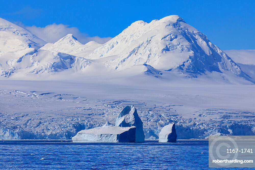 Non-tabular iceberg off glaciated, mountainous Anvers Island, blue sky, Antarctic Peninsula, Antarctica, Polar Regions