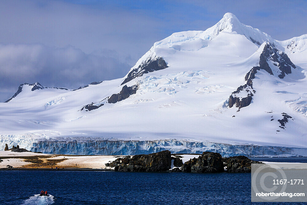 Tourists on a zodiac boat approach Half Moon Island, Livingston Island mountain backdrop, South Shetland Islands, Antarctica