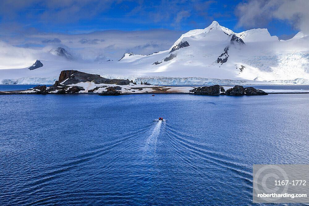 Tourists on a zodiac boat approach Half Moon Island, Livingston Island mountain backdrop, South Shetland Islands, Antarctica, Polar Regions