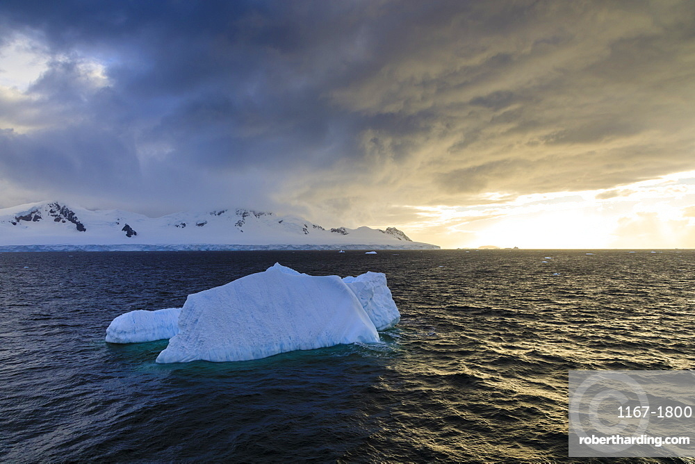 Blue iceberg at sunset, with interesting cloud formations, Gerlache Strait, Antarctic Peninsula, Antarctica, Polar Regions