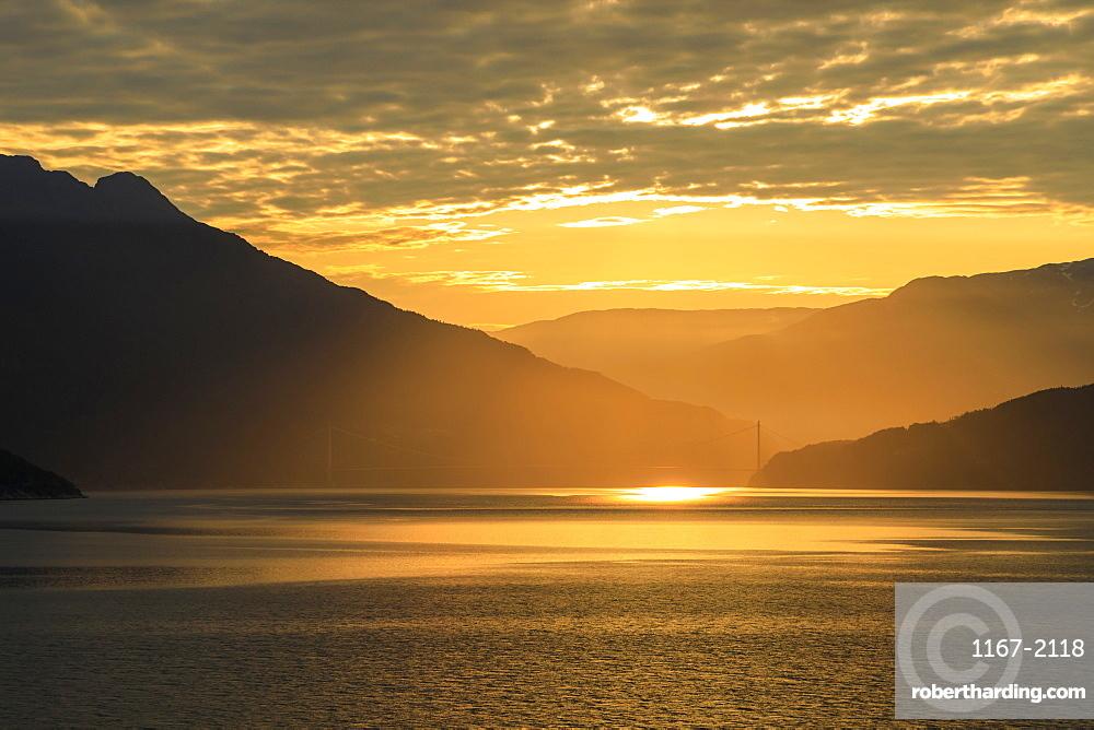 Stunning sunrise over the huge Hardanger Bridge, misty dawn, beautiful clouds, Hardangerfjord, Norwegian Western Fjords, Norway, Scandinavia, Europe
