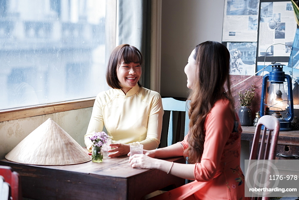 Two friends in Ao Dai dresses taking coffee in a Saigon coffee house, Ho Chi Minh City, Vietnam, Indochina, Southeast Asia, Asia