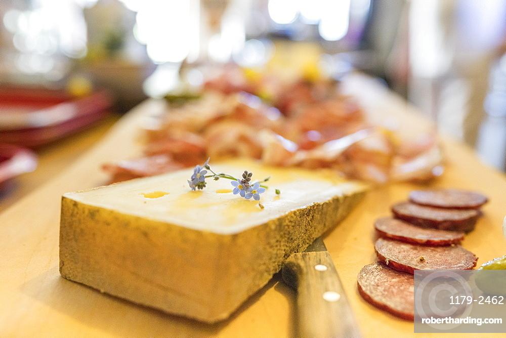Typical salami and cheese on chopping board, San Romerio Alp, Brusio, Canton of Graubunden, Poschiavo Valley, Switzerland, Europe