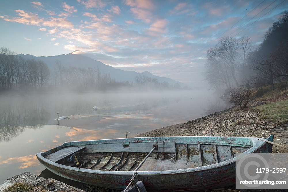 Wood boat on the shore of River Mera at sunrise, Sorico, Como province, Lower Valtellina, Lombardy, Italy, Europe