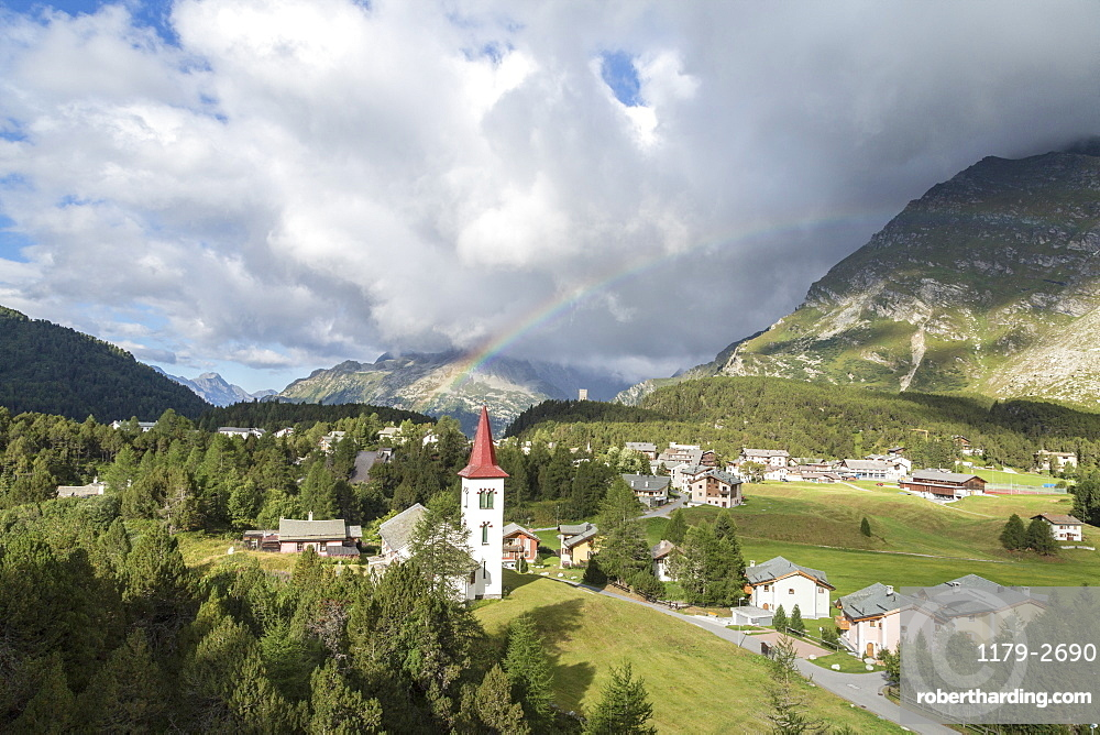 Rainbow over Chiesa Bianca and the village of Maloja, Bregaglia Valley, Canton of Graubunden, Engadin, Switzerland