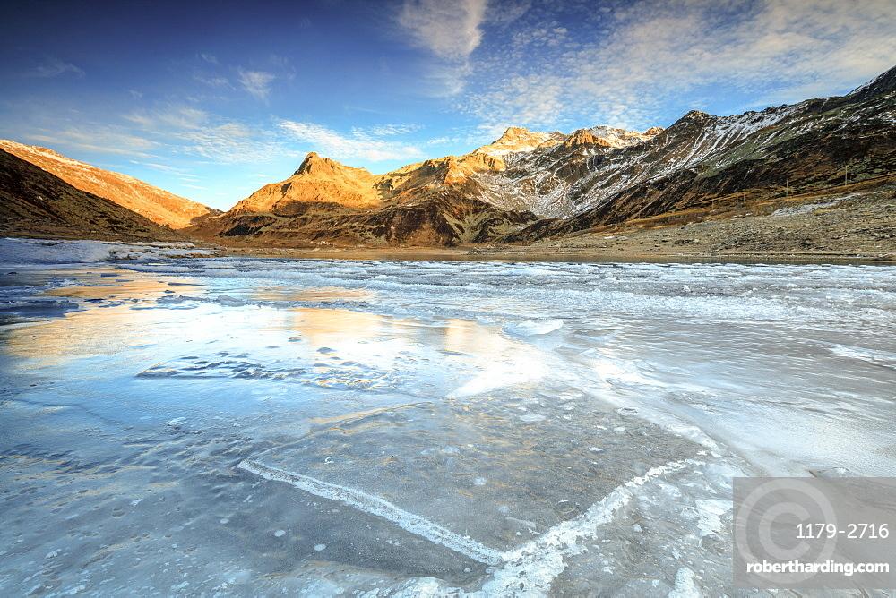 Frozen lake Montespluga at dawn, Chiavenna Valley, Sondrio province, Valtellina, Lombardy, Italy, Europe