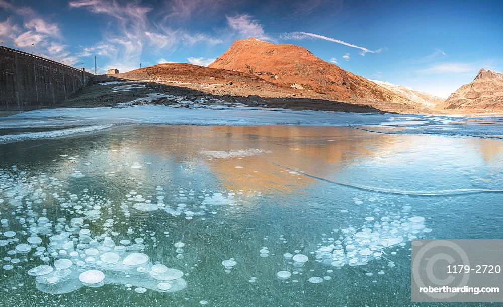 Panoramic of frozen lake Montespluga at dawn, Chiavenna Valley, Sondrio province, Valtellina, Lombardy, Italy, Europe