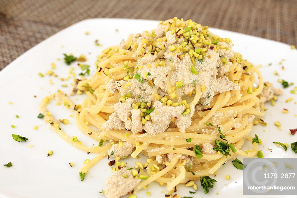 Pasta on platter with swordfish eggs garnished with Bronte pistachio, Sicily, Italy