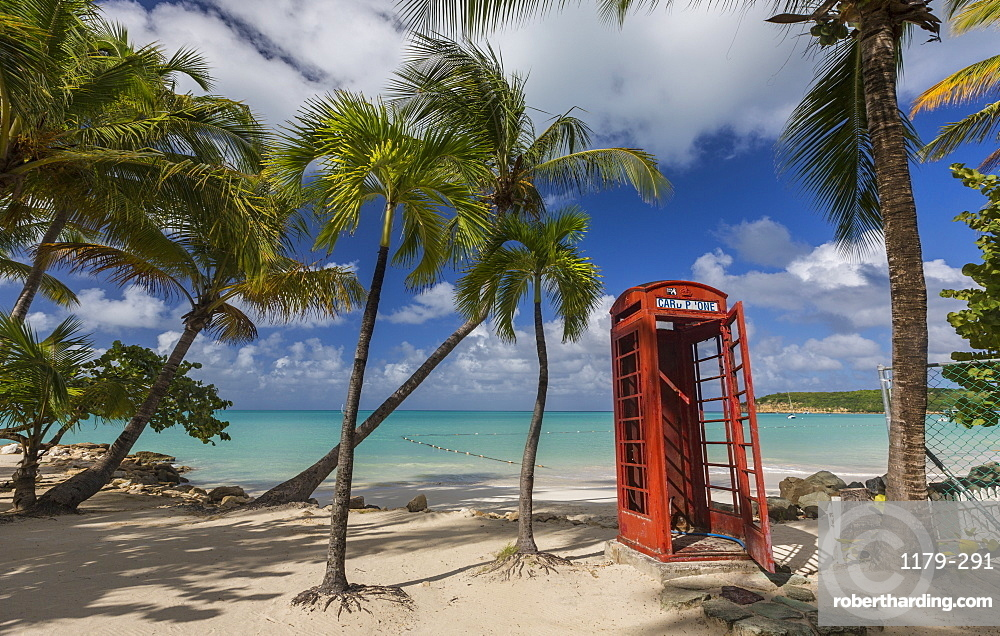 A red telephone box lies abandoned under coconut trees that surround Dickenson Bay, a strip of sand overlooking the Caribbean Sea, Antigua, Leeward Islands, West Indies, Caribbean, Central America