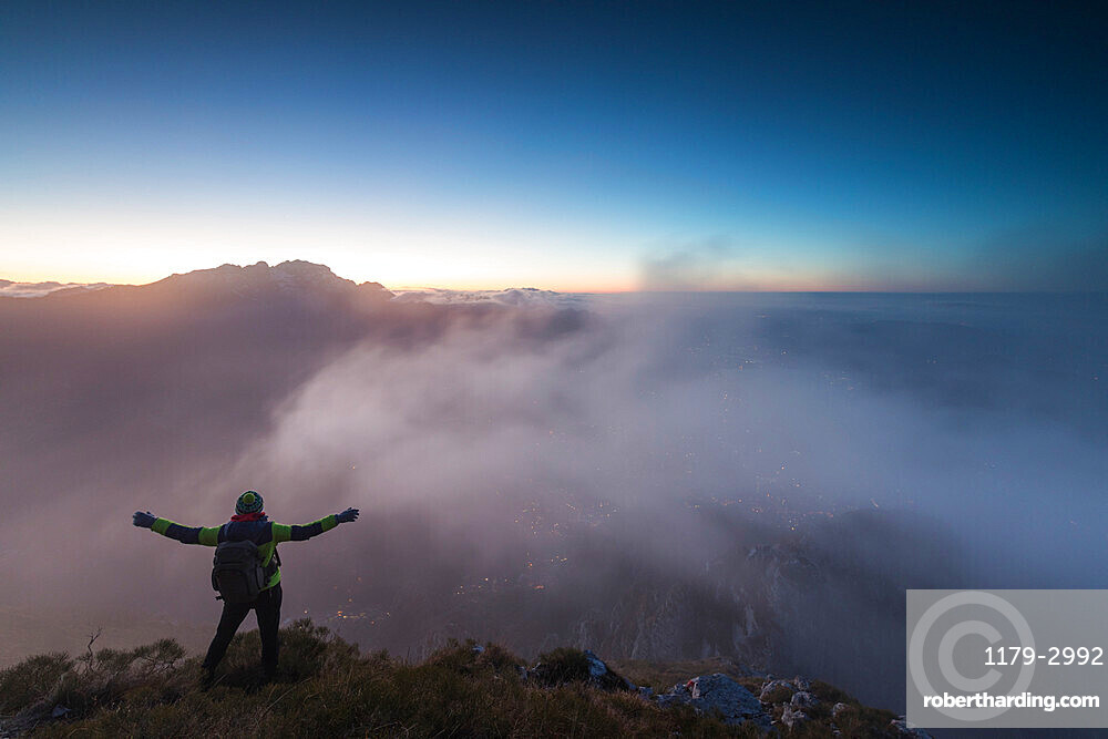 Hiker on top of Monte Coltignone at dawn, province of Lecco, Lombardy, Italy, Europe