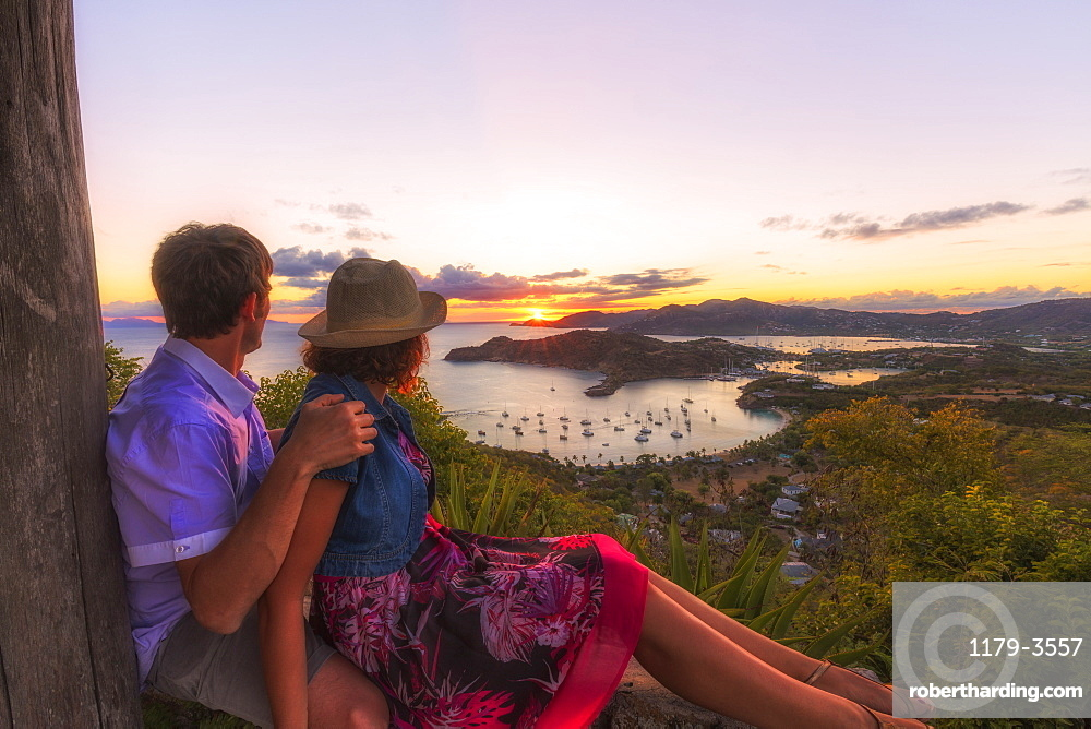 Couple look across English Harbour from Shirley Heights at sunset, Antigua, Antigua and Barbuda, Leeward Islands, West Indies, Caribbean, Central America