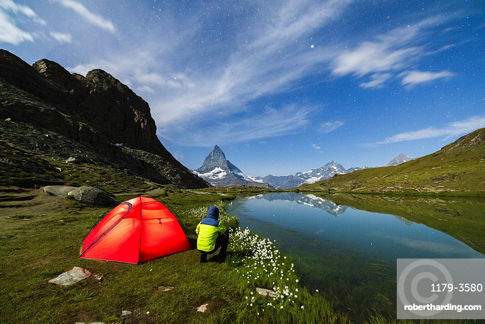 Hiker beside tent looking towards the Matterhorn from lake Riffelsee, Zermatt, canton of Valais, Swiss Alps, Switzerland, Europe