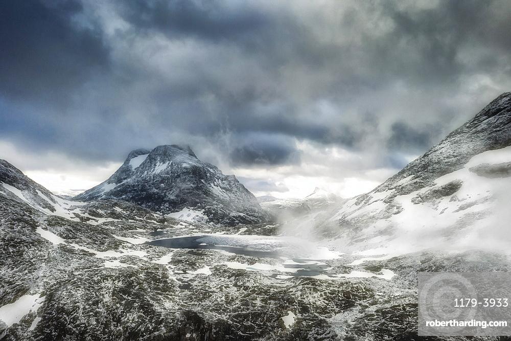 Storm clouds over Olaskarsvatnet lake at feet of the snowcapped Olaskarstind mountain, Venjesdalen valley, Andalsnes, Norway, Scandinavia, Europe