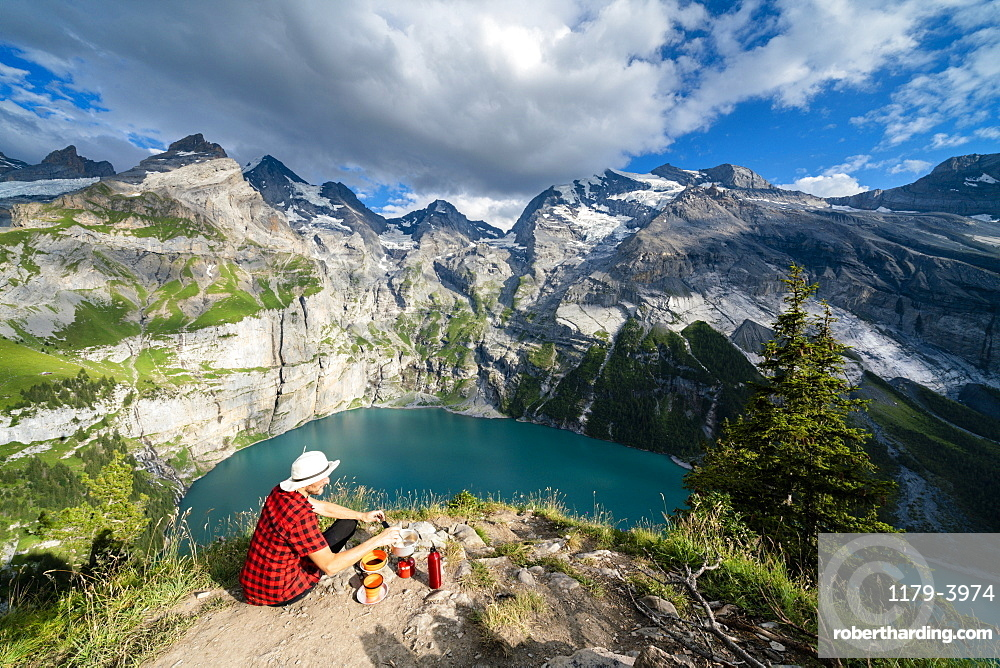 Hiker cooking food on camping stove high up above Oeschinensee lake, Bernese Oberland, Kandersteg, Canton of Bern, Switzerland