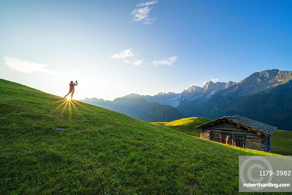 Man lit by the sunburst photographing Piz Badile and Cengalo, Tombal, Soglio, Val Bregaglia, canton of Graubunden, Switzerland