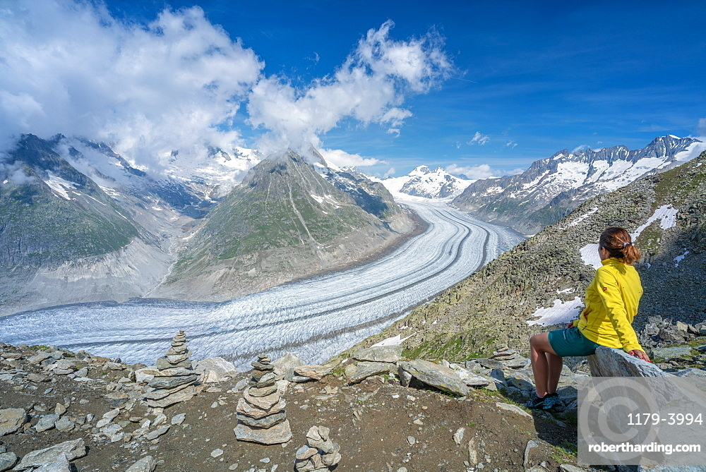 Side view of woman sitting on rocks admiring Aletsch Glacier from Eggishorn viewpoint, Bernese Alps, canton Valais, Switzerland