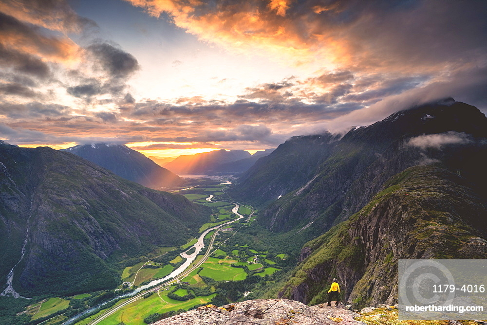 Elevated view of man standing on Romsdalseggen ridge admiring Rauma valley during sunset, Andalsnes, More og Romsdal, Norway