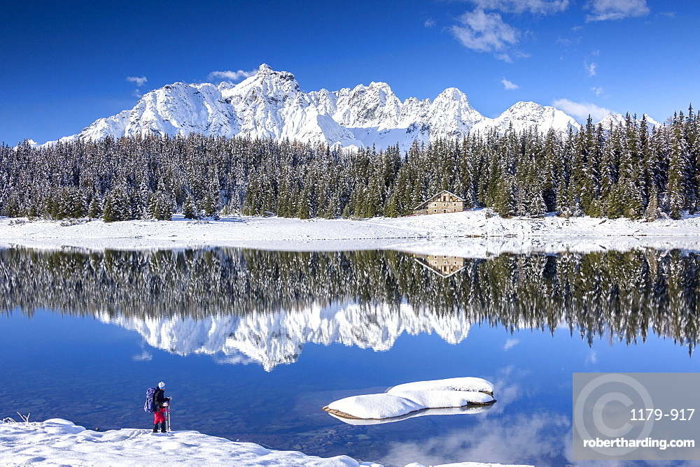 Hiker admires the snowy peaks and woods reflected in Lake Palu, Malenco Valley, Valtellina, Lombardy, Italy, Europe