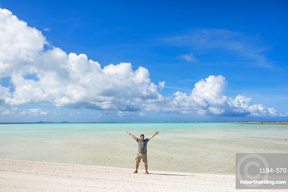 Man standing on a white sand beach in the lagoon of Wallis, Wallis and Futuna, Pacific