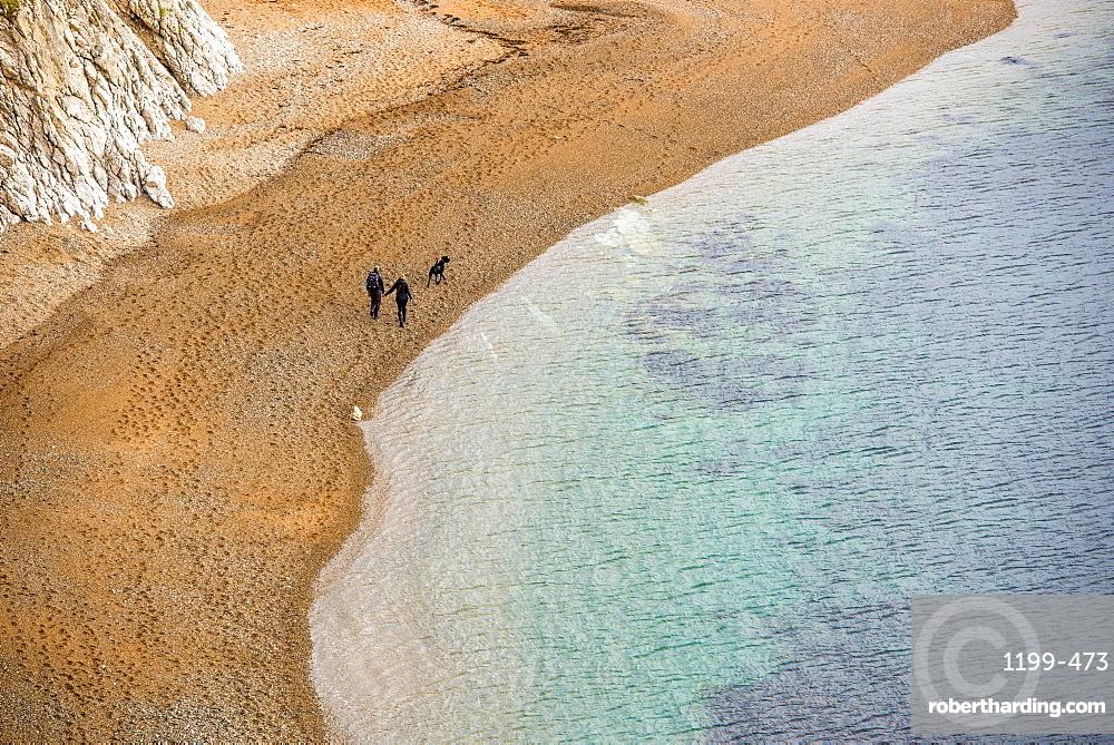 Couple and dog walking along the beach, Jurassic Coast, UNESCO World Heritage Site, Dorset, England, United Kingdom, Europe