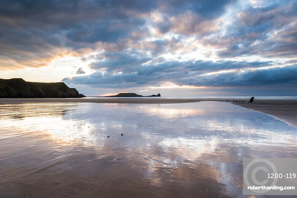 Sunset clouds reflected in wet sand, Rhossili Bay, Gower Peninsula, South Wales.