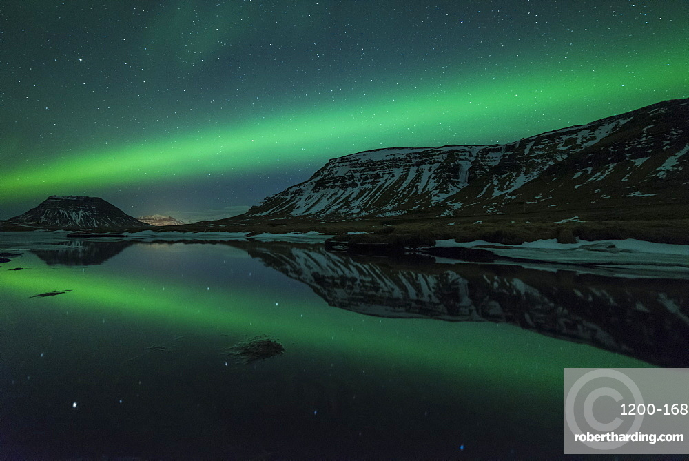 Aurora borealis reflecrted in partially frozen lake, North Snaefellsnes, Iceland.