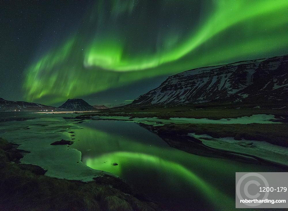 Aurora borealis reflecrted in partially frozen lake, North Snaefellsnes, Iceland.
