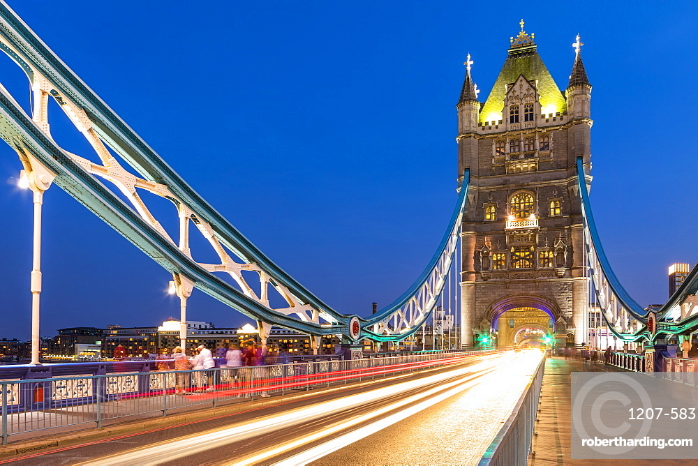 Traffic driving over Tower Bridge in early evening light, London, England, United Kingdom, Europe