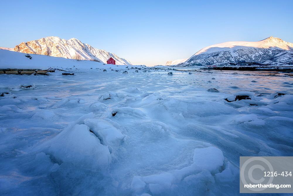 Rorbuer (fisherman's hut) on a frozen lake, Lofoten, Nordland, Arctic, Norway, Europe