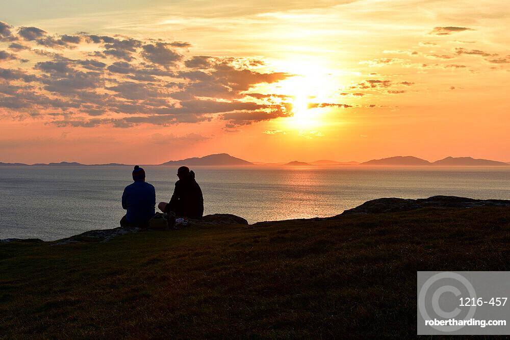 Two tourists enjoying a beautiful sunset at Neist Point on the Isle of Skye, Outer Hebrides, Scotland, UK