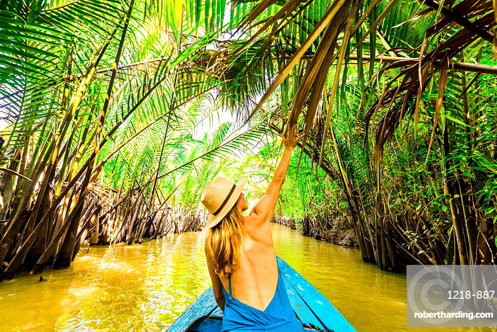 Sailing through some of the tributaries of the Mekong River to get to a village to see how they make coconut candy.
