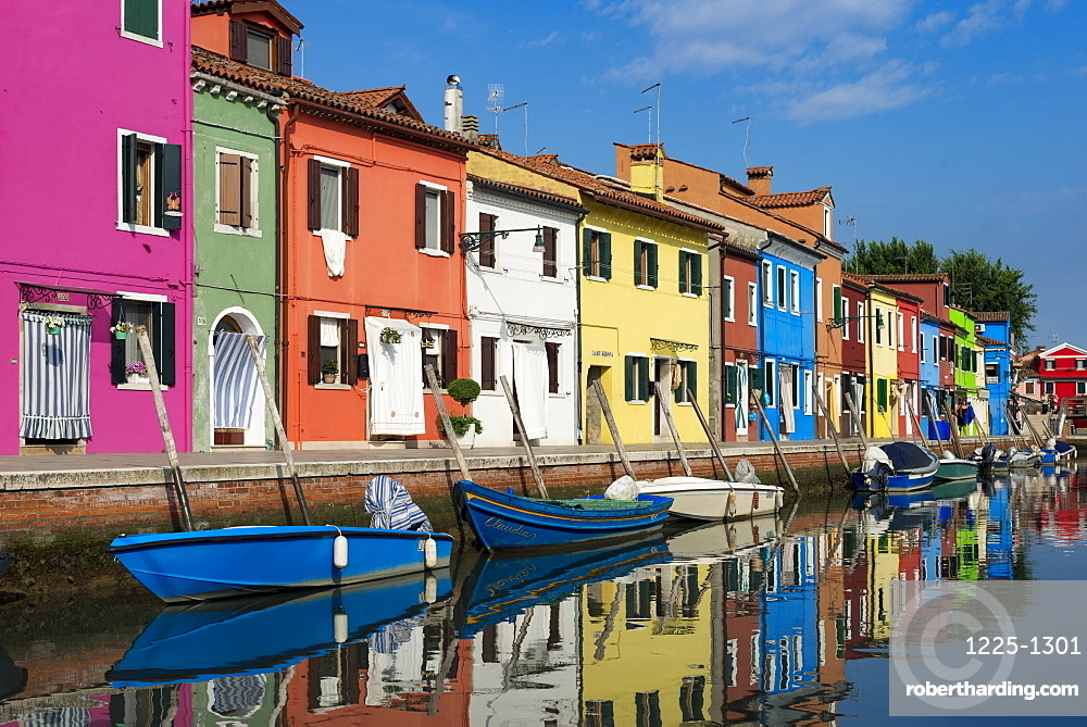 Colourful Burano houses and boats reflected in a canal, Venice, Veneto, Italy, Europe