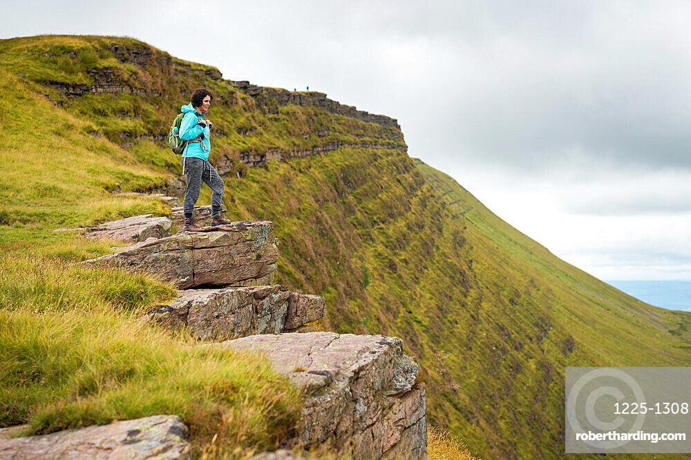 A woman looks out from a high escarpment while hiking in the Brecon Beacons National Park mountain range