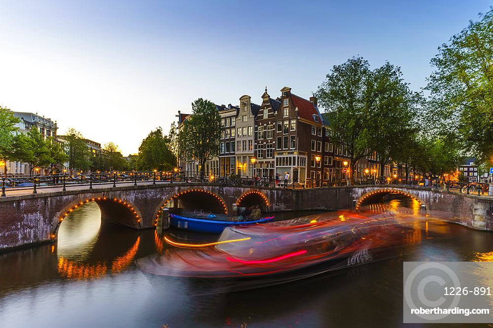Keizersgracht canal at dusk, trailing light blur from a tourist boat, Amsterdam, Netherlands