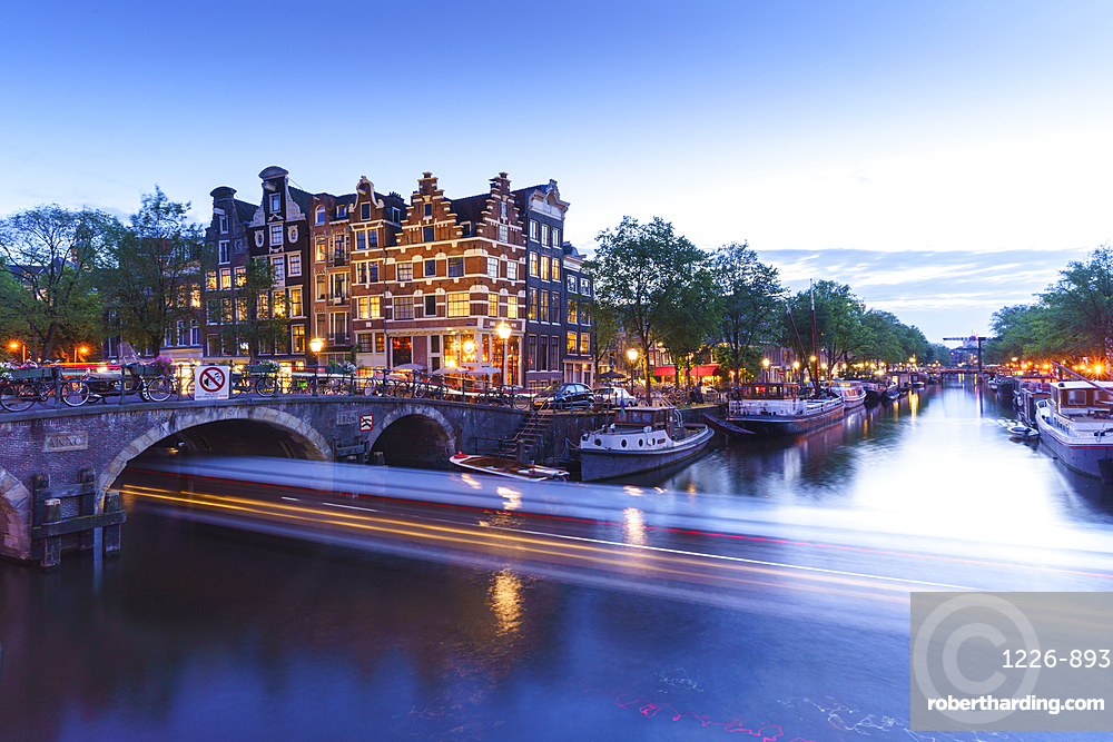 Dusk on Brouwersgracht canal with trailing light from a tourist boat passing under a bridge, Amsterdam, Netherlands