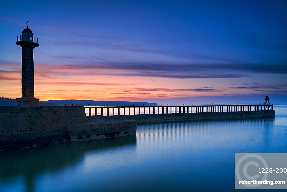 Sunset afterglow over Whitby west pier and lighthouse, the North Yorkshire coast, England.