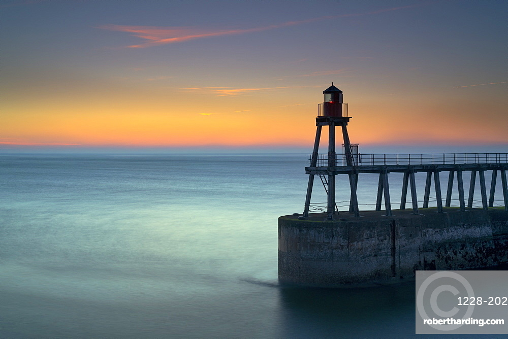 Daybreak over Whitby east pier and lighthouse, North Yorkshire, England.