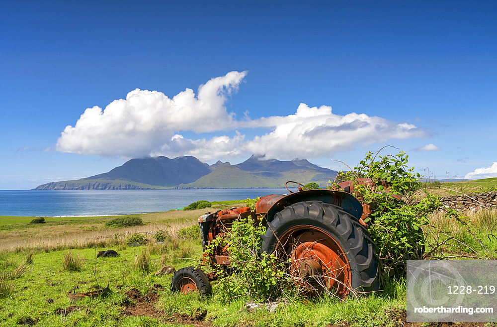 An abandoned tractor on a Cleadale Croft, with distant view of The Isle of Rhum in mid-summer.
