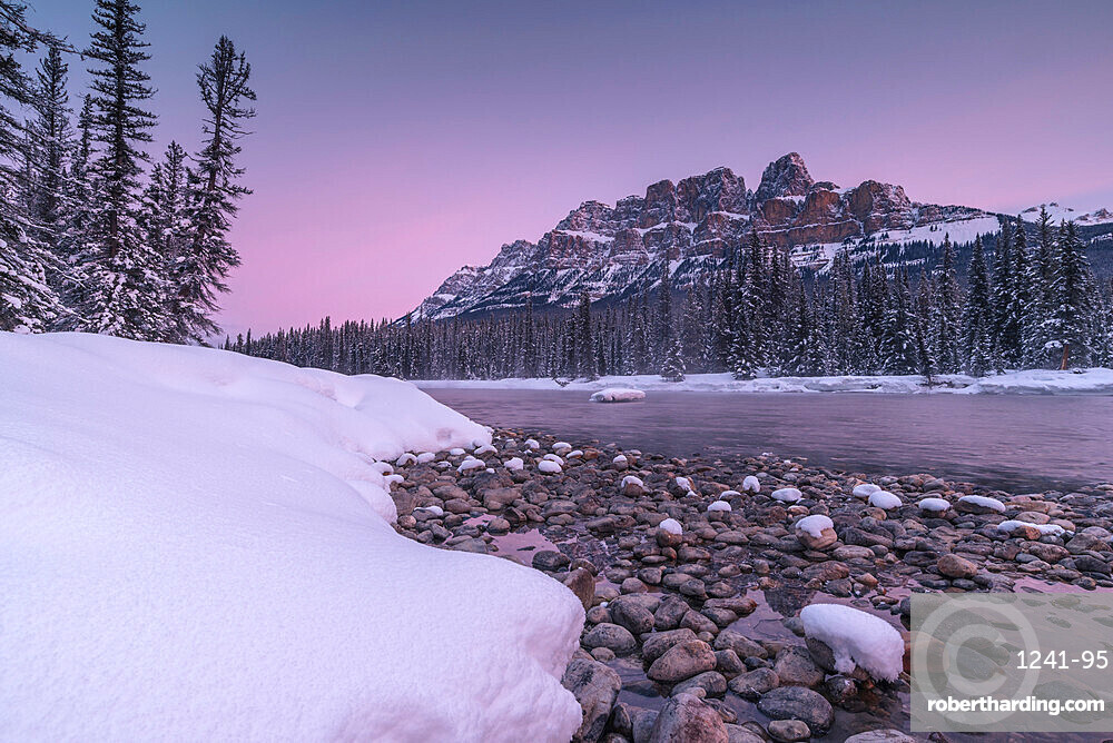 Sunrise and snowy landscape during winter at Bow River and Castle Mountain in Banff National Park, Alberta, Canada