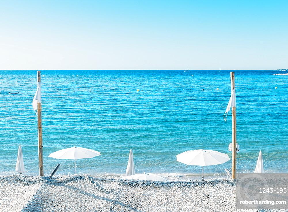 Giant white beach umbrella next to the ocean against a blue sky in Juan les Pins, Cote d'Azur, Provence, France, Mediterranean, Europe