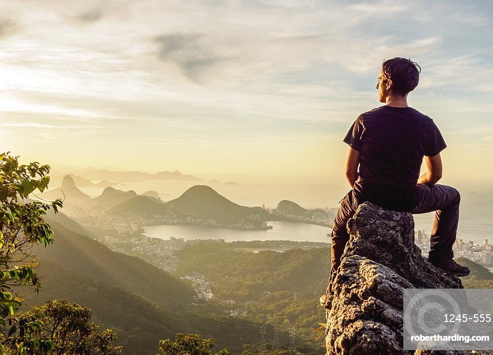 Hiker enjoying the view of Rio de Janeiro from Pedra da Proa, Tijuca Forest National Park, State of Rio de Janeiro, Brazil, South America