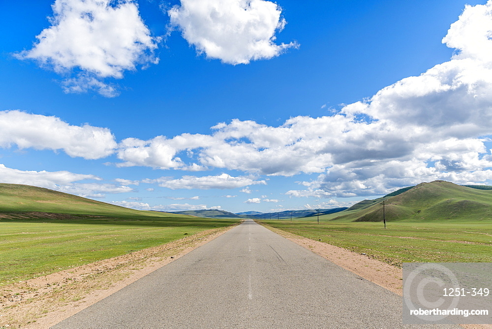 Straight road in the Mongolian steppe and clouds in the sky, North Hangay province, Mongolia, Central Asia, Asia