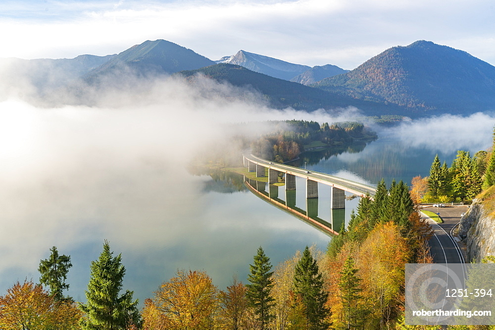 Sylvenstein Lake and bridge surrounded by the morning mist. Bad Tölz-Wolfratshausen district, Bavaria, Germany.
