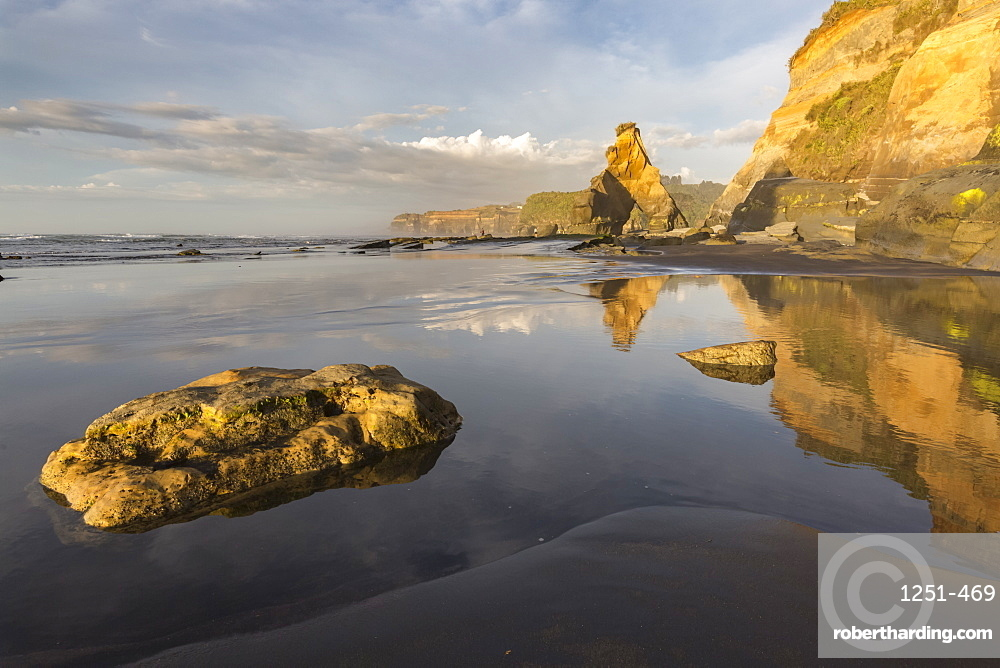Rock formations reflect with low tide. Tongaporutu, New Plymouth district. Taranaki region, North Island, New Zealand.