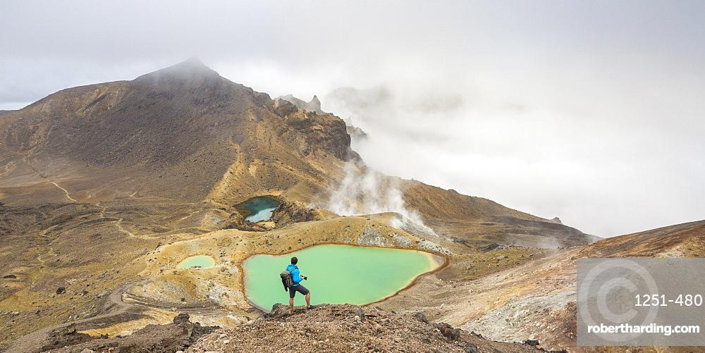 Man taking photos of Emerald Lakes. Tongariro Alpine Crossing, Tongariro NP, Waikato region, North Island, New Zealand.