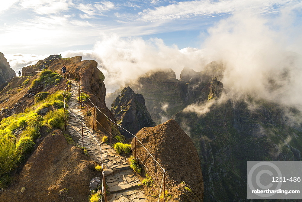 Hikers walking on Vereda do Areeiro, the trail that links Pico Ruivo to Pico do Arieiro, Funchal, Madeira region, Portugal.